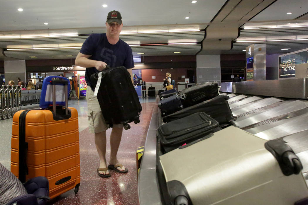 Bill McClain of San Diego, Calif., grabs his luggage at baggage claim in McCarran International Airport, which just received a top ranking for quality from J.D. Power & Associates, Friday, Oct., 1 ...