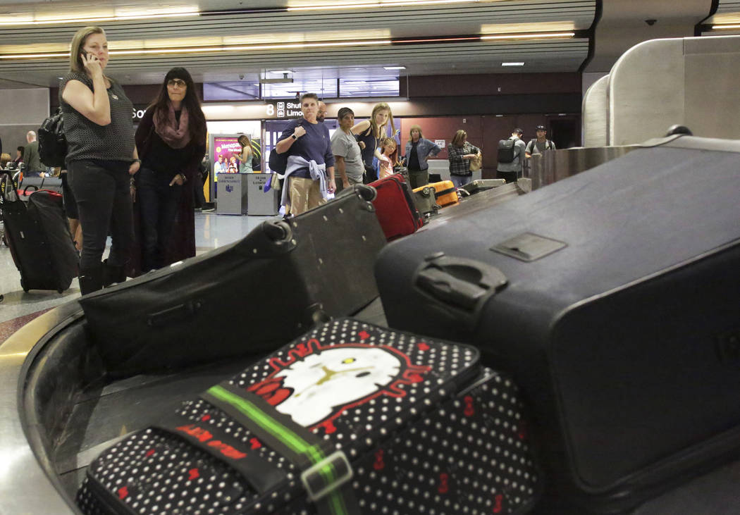 Marriah Pearson, left, of Temecula, Calif., and Cheryl Bowman of Carlsbad, Calif., wait for their luggage at baggage claim in McCarran International Airport, which just received a top ranking for ...