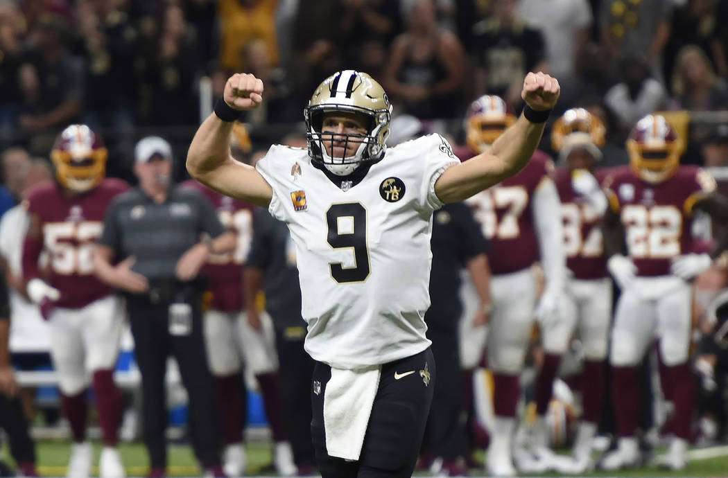 New Orleans Saints quarterback Drew Brees (9) reacts to a touchdown carry by running back Mark Ingram, not pictured, in the first half of an NFL football game against the Washington Redskins in Ne ...