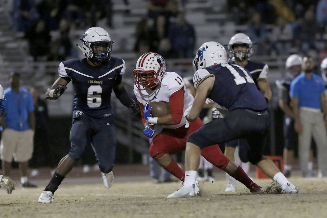 Liberty High's wide receiver Zanden Shim (11) tries to avoid a tackle from Foothill High's Jordan Wilson (6) and linebacker Ollie Chori (11) during their game on Friday, Oct. 19 , 2018, in Henders ...