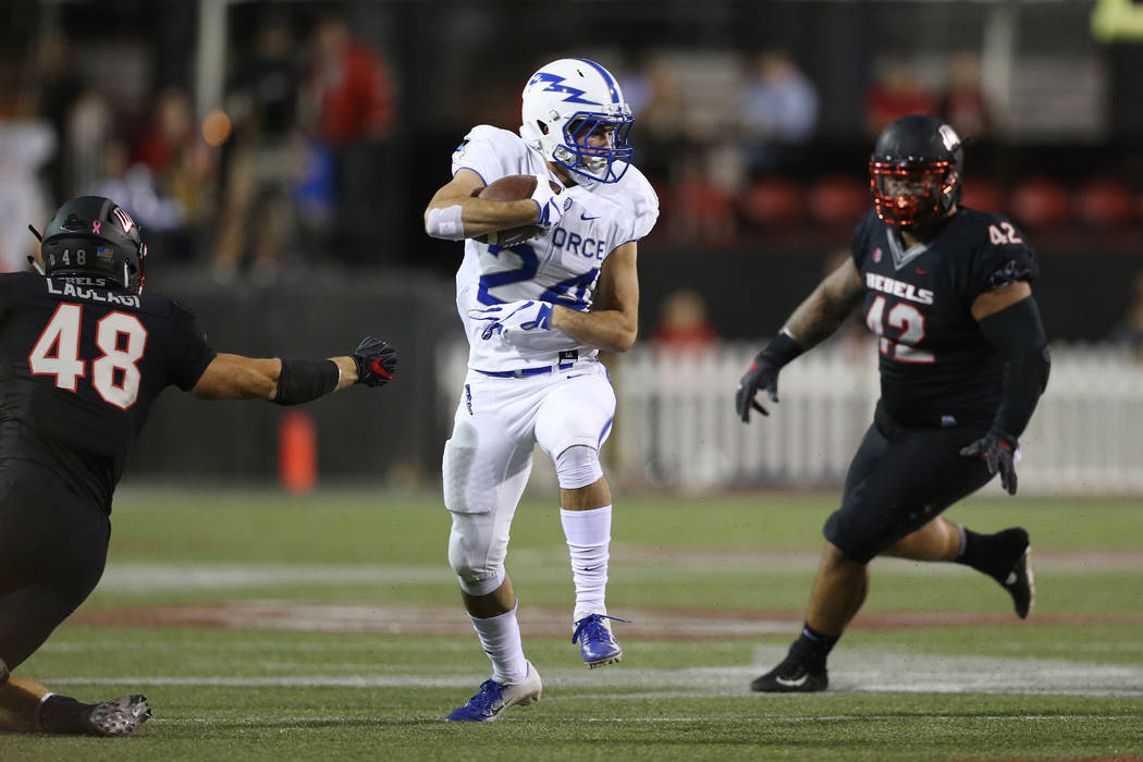 Air Force Falcons running back Kadin Remsberg (24) runs the ball during the first quarter against coverage from UNLV Rebels linebacker Bailey Laolagi (48) and defensive lineman Salanoa-Alo Wily (4 ...