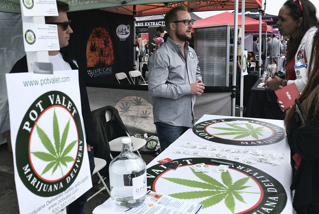 A booth advertises a delivery service for cannabis at the Four Twenty Games in Santa Monica, Calif., in March 2018. (AP Photo/Richard Vogel, File)
