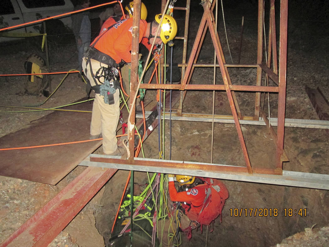 A rescue team lowers themselves into an old abandoned mine shaft to rescue a man who fell into the shaft on Monday, Oct. 15, 2018, the near Aguila, Ariz. (Maricopa County Sheriff's Office via AP)