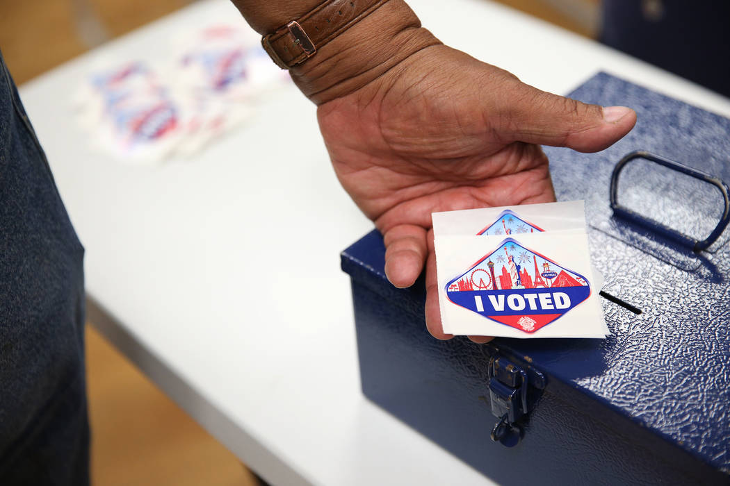 "Poll worker Myron Wilson holds ""I Voted"" stickers at the East Las Vegas Community Center in Las Vegas, Saturday, Oct. 20, 2018. Erik Verduzco Las Vegas Review-Journal @Erik_Verduzco"