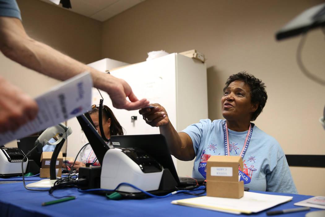 Poll worker Robin Wright hands out a voter card at the East Las Vegas Community Center in Las Vegas, Saturday, Oct. 20, 2018. Erik Verduzco Las Vegas Review-Journal @Erik_Verduzco