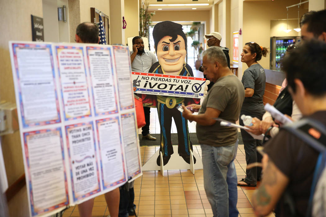 A cardboard cutout of the Las Vegas Lights mascot Cash the Soccer Rocker greets people waiting in line to vote early at the East Las Vegas Community Center in Las Vegas, Saturday, Oct. 20, 2018. E ...
