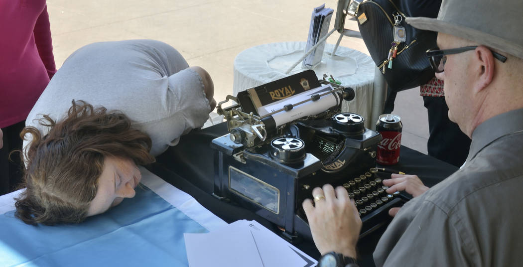 Madison Greenstein, 15, of Henderson checks out the inner workings of a 1940s-era Royal typewriter through a window on its side as author Sean Hoade works on a haiku during the Las Vegas Book Fest ...