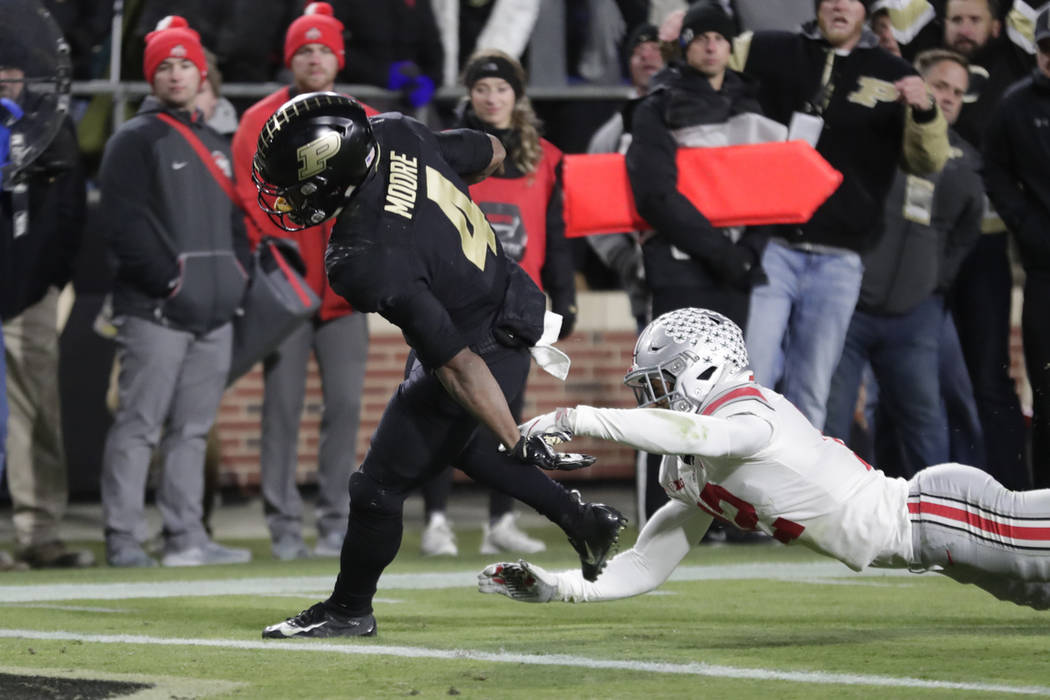 Purdue wide receiver Rondale Moore (4) scores a touchdown after breaking the tackle of Ohio State safety Isaiah Pryor (12) during the first half of an NCAA college football game in West Lafayette, ...