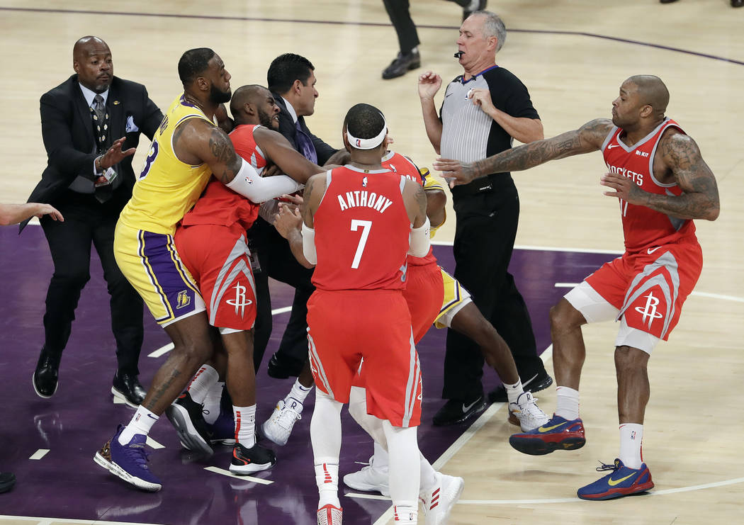 Houston Rockets' Chris Paul, second from left, is held back by Los Angeles Lakers' LeBron James, left, as Paul fights with Lakers' Rajon Rondo, center obscured, during the second half of an NBA ba ...