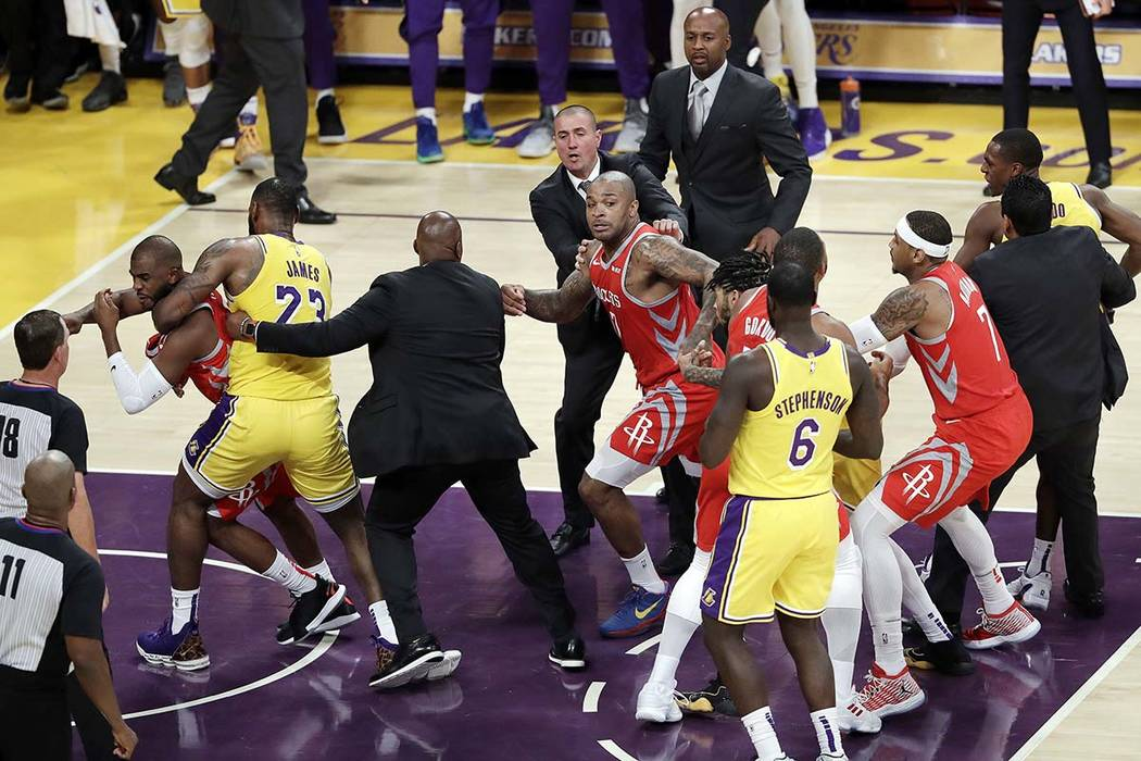 Houston Rockets' Chris Paul, far left, is held back by Los Angeles Lakers' LeBron James, second from left, after Paul fought with Lakers' Rajon Rondo, far right, during the second half of an NBA b ...