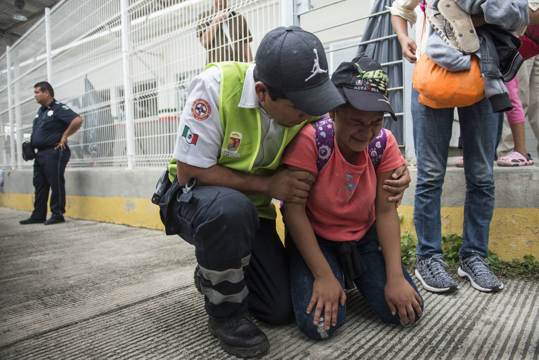 A Honduras migrant is comforted by a Mexican paramedic after her mother fainted while crossing the border between Guatemala and Mexico, in Ciudad Hidalgo, Mexico, Saturday, Oct. 20, 2018. Mexican ...