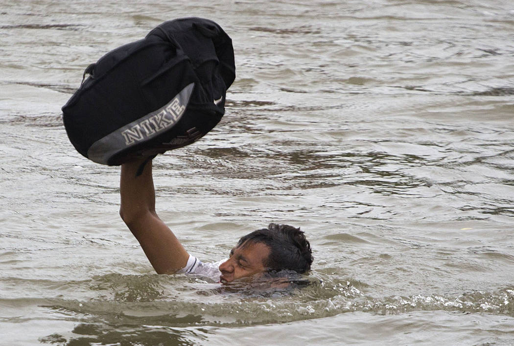 A Central American migrant wades across the Suchiate River, on the the border between Guatemala and Mexico, in Ciudad Hidalgo, Mexico, Saturday, Oct. 20, 2018. After Mexican authorities slowed acc ...