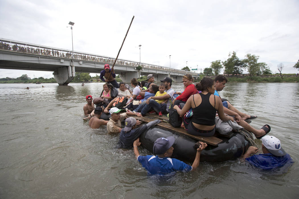 A group of Central American migrants cross the Suchiate River aboard a raft made out of tractor inner tubes and wooden planks, on the the border between Guatemala and Mexico, in Ciudad Hidalgo, Me ...