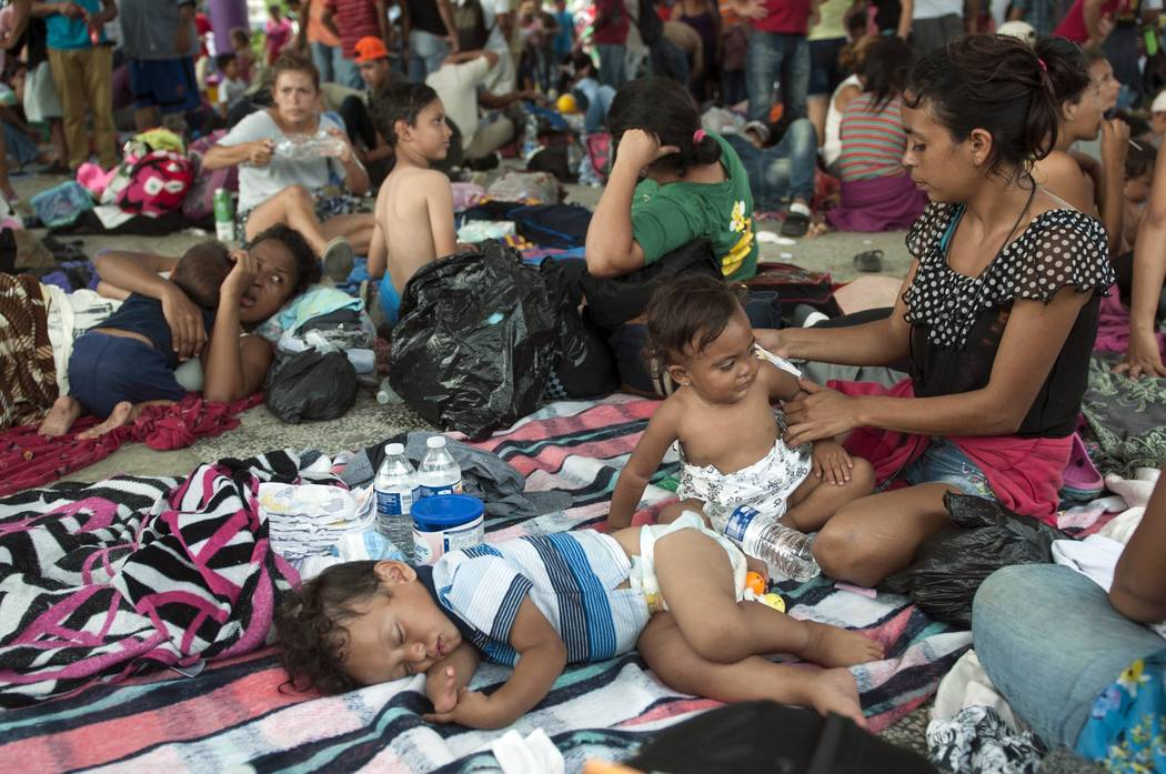 A group of migrants rests at the central park in Ciudad Hidalgo, Mexico, Saturday, Oct. 20, 2018. About 2,000 Central American migrants who circumvented Mexican police at a border bridge and swam, ...