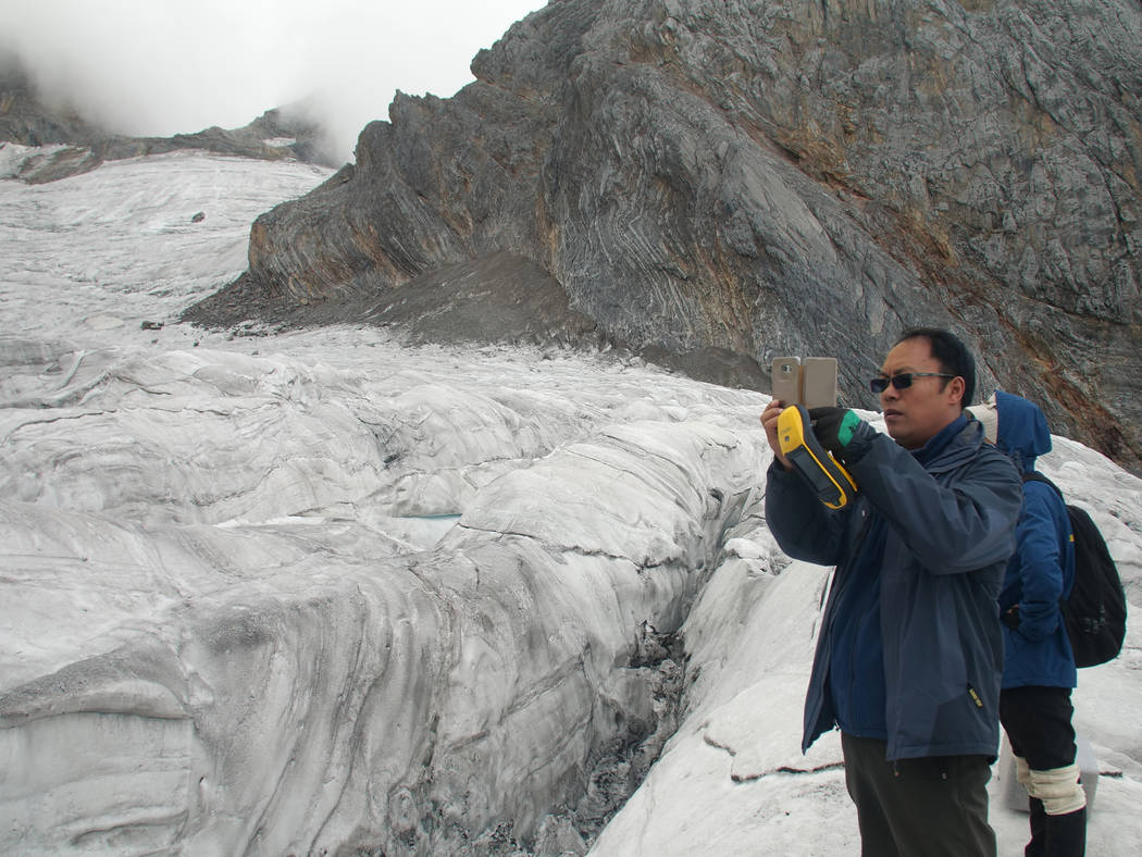 This Sept. 22, 2018 photo shows glaciologist Wang Shijin photographing the Baishui Glacier No.1 on the Jade Dragon Snow Mountain in the southern province of Yunnan in China. Scientists say the gla ...