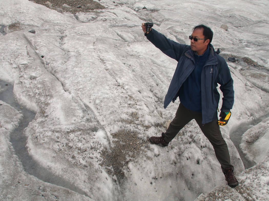 This Sept. 22, 2018 photo shows glaciologist Wang Shijin photographing an ice crevasse in the Baishui Glacier No. 1 on the Jade Dragon Snow Mountain in the southern province of Yunnan in China. Sc ...