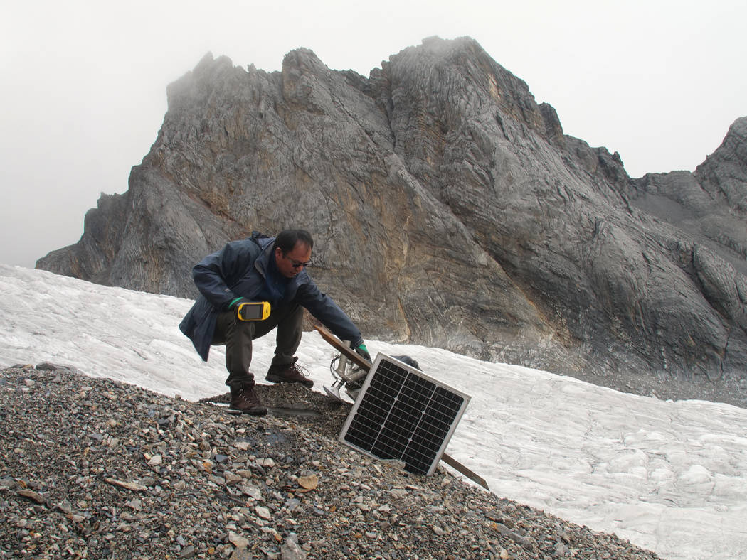 This Sept. 22, 2018 photo shows glaciologist Wang Shijin repairing a broken remote meteorological station on the Baishui Glacier No. 1 on the Jade Dragon Snow Mountain in the southern province of ...
