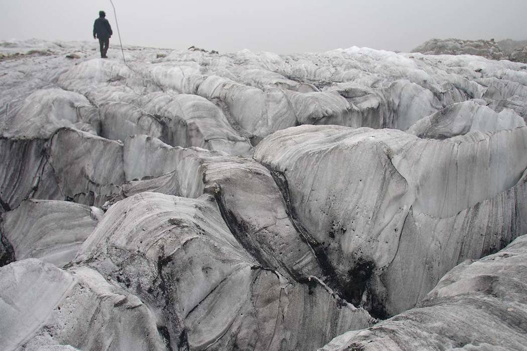 In this Sept. 22, 2018 photo, glaciologist Wang Shijin walks across the Baishui Glacier No.1 on Jade Dragon Snow Mountain in the southern province of Yunnan in China. Scientists say the glacier is ...