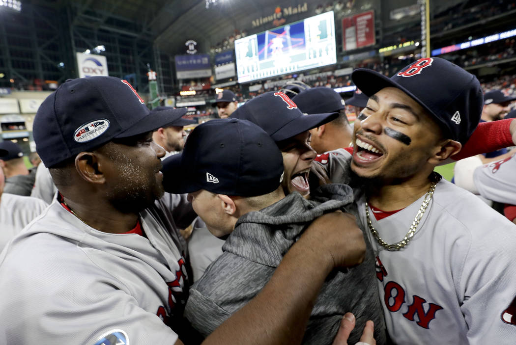Boston Red Sox right fielder Mookie Betts, right, celebrates after they won the baseball American League Championship Series against the Houston Astros on Thursday, Oct. 18, 2018, in Houston. Red ...