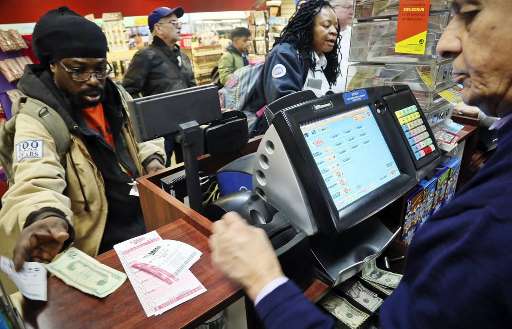 Lottery players buy Mega Millions lottery tickets Friday Oct. 19, 2018, in New York. The estimated jackpot for Friday's drawing has soared to $1 billion. (AP Photo/Bebeto Matthews)