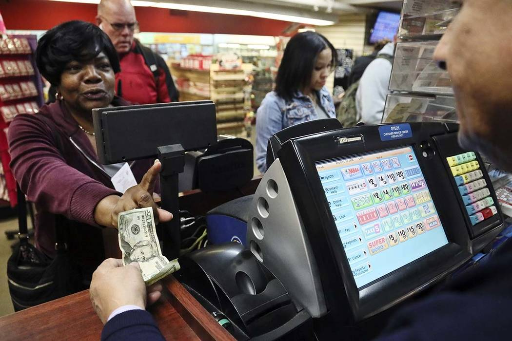 Annette Gray, left, from Valley Stream, N.Y., buys lottery tickets Friday Oct. 19, 2018, in New York. The estimated jackpot for Friday's Mega Millions drawing has soared to $1 billion. Gray said i ...