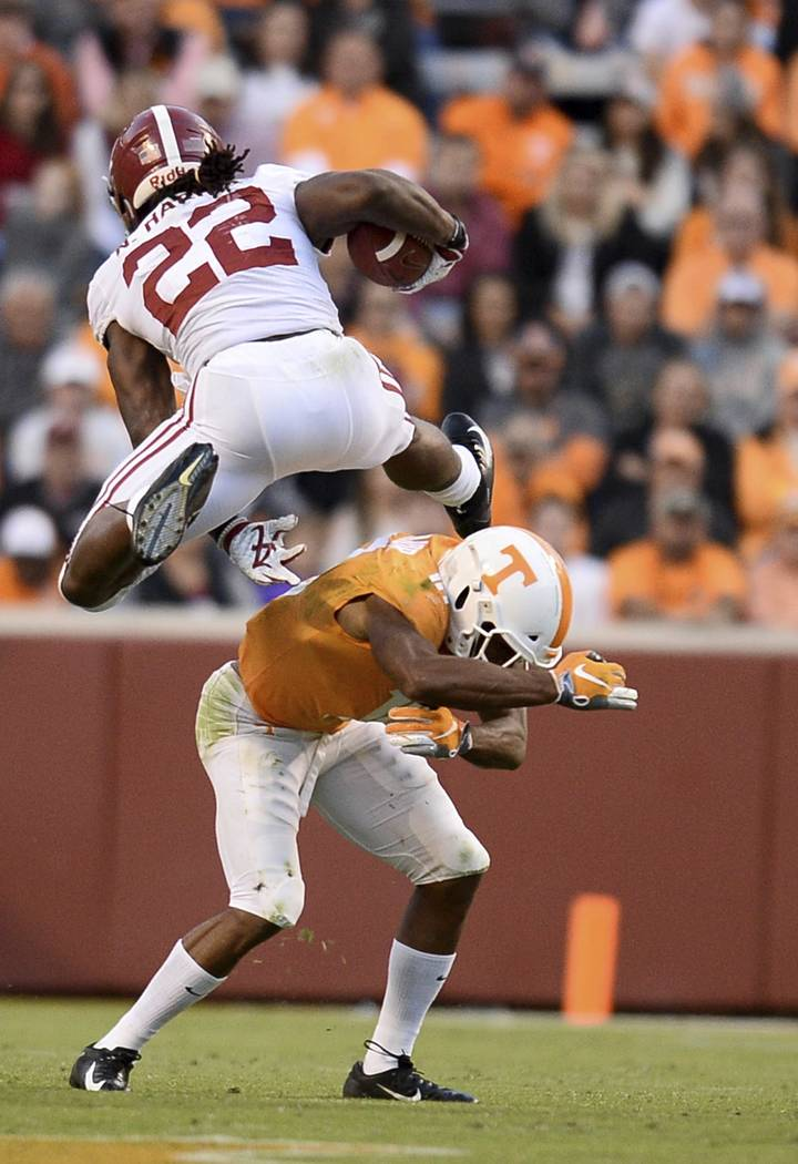 Alabama running back Najee Harris (22) hurtles over Tennessee defensive back Nigel Warrior (18) as he runs toward the end zone during the second half of an NCAA college football game Saturday, Oct ...