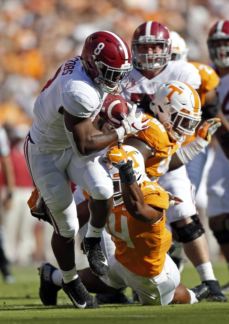 Alabama running back Josh Jacobs (8) runs for yardage as he's hit by Tennessee linebacker Quart'e Sapp (14) in the first half of an NCAA college football game Saturday, Oct. 20, 2018, in Knoxville ...