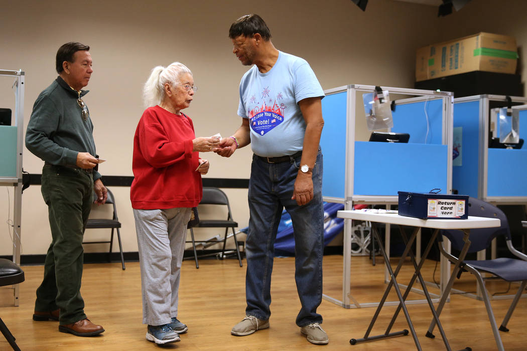 "Voters Rudy De Leon and Esther French receive ""I Voted"" stickers from poll worker Myron Wilson at the East Las Vegas Community Center in Las Vegas, Saturday, Oct. 20, 2018. Erik Verduzco Las Vegas ..."