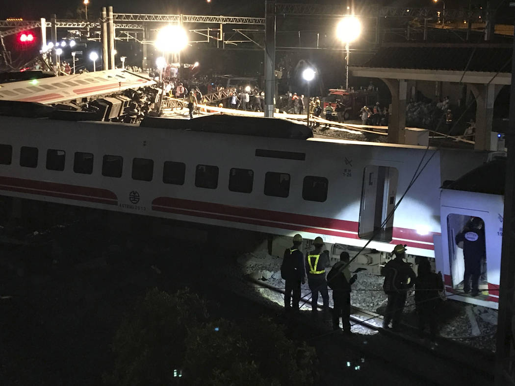 Rescue workers gather at the site of a train derailment in Lian county in northern Taiwan on Sunday, Oct. 21, 2018. Passengers were killed and injured on Sunday when one of Taiwan's newer, faster ...