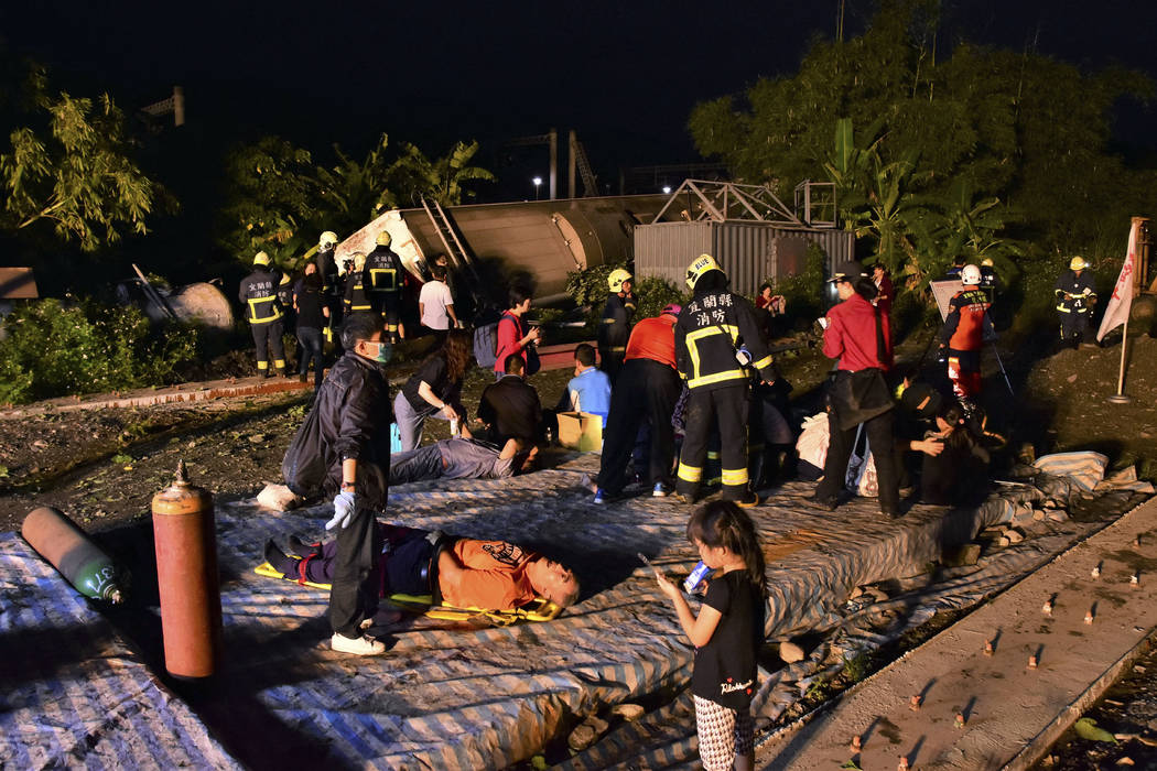 Rescue workers tend to the injured at the site of a train derailment in Lian county in northern Taiwan on Sunday, Oct. 21, 2018. Passengers were killed and injured on Sunday when one of Taiwan's n ...