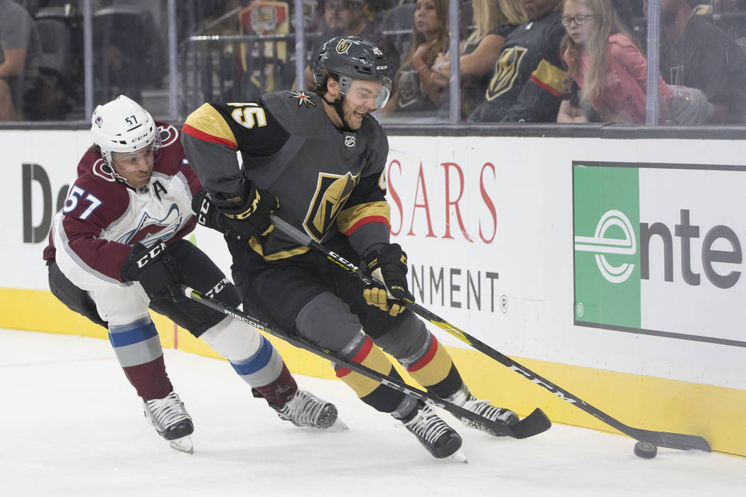 Golden Knights defenseman Jake Bischoff (45) fights for possession with Colorado Avalanche left wing Gabriel Bourque (57) in the first period during their NHL preseason matchup on Monday, Sept. 24 ...