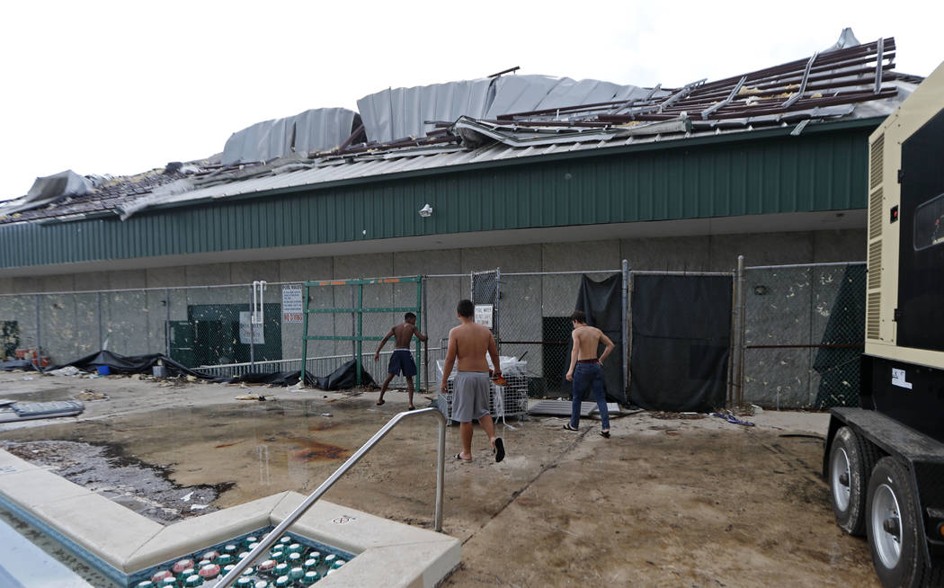 Mosley high football team members arrive for practice at their heavily damaged school, in the aftermath of Hurricane Michael in Lynn Haven, Fla., Friday, Oct. 19, 2018. (AP Photo/Gerald Herbert)