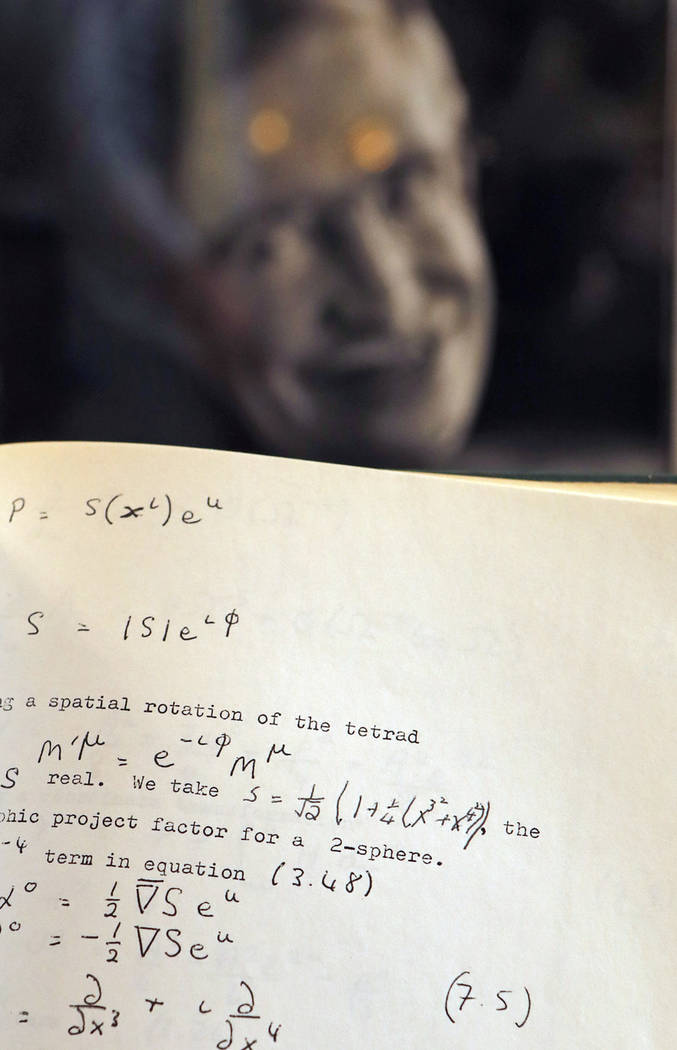 A Book, written and corrected with handwritten annotation by Stephen Hawking is one of the personal and academic possessions of Stephen Hawking, photo behind, on display at the auction house Chris ...