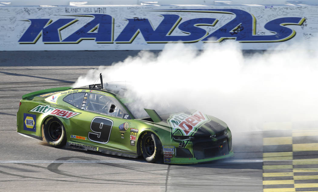 Chase Elliott (9) does a burnout after winning a NASCAR Cup Series auto race at Kansas Speedway in Kansas City, Kan., Sunday, Oct 21, 2018. (AP Photo/Colin E. Braley)