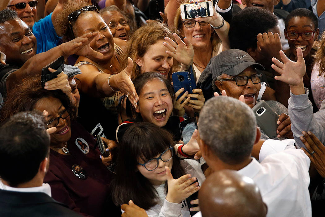 People clamor to shake hands with Former President Barack Obama at a rally in support of candidate for Senate Jacky Rosen and other Nevada Democrats, Monday, Oct. 22, 2018, in Las Vegas. (AP Photo ...