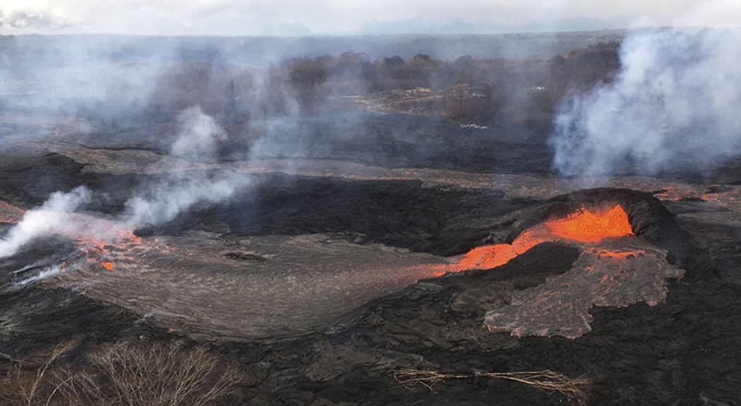 Lava fountains have built a small spatter cone, the black mound at right, from which lava spills out onto the surface and flows into a small pond at left, in Kilauea Volcano near the town of Pahoa ...