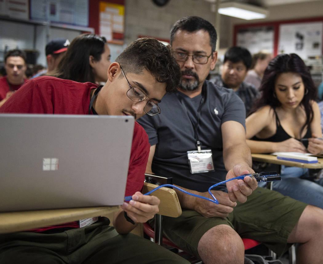 Emmanuel Munoz, left, and Angelo Carvalho plug in a cord to a laptop during a session introducing Arduino, an open-source electronics platform, at UNLV's Make-A-Thon in Las Vegas, Saturday, Oct. 2 ...
