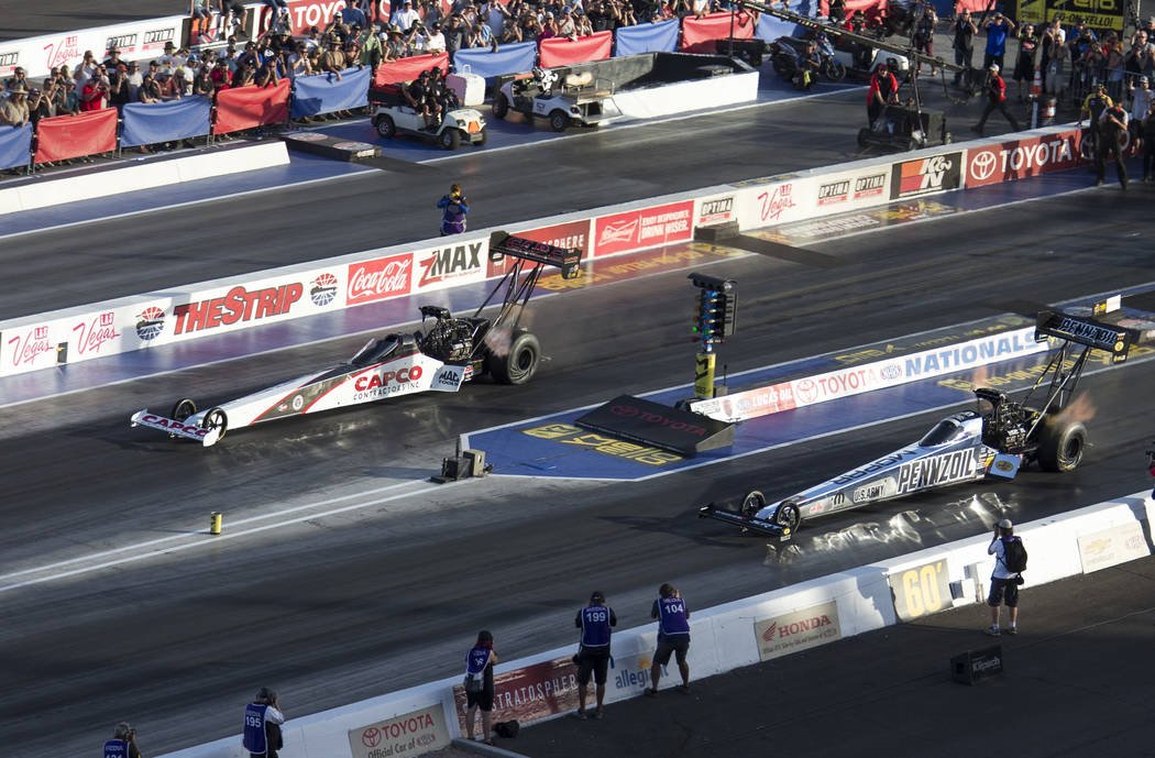 NHRA Top Fuel Dragster driver Steve Torrence, top, races ahead of Leah Pritchett to win the Top Fuel championship race at NHRA Toyota Nationals at The Strip at Las Vegas Motor Speedway on Sunday, ...