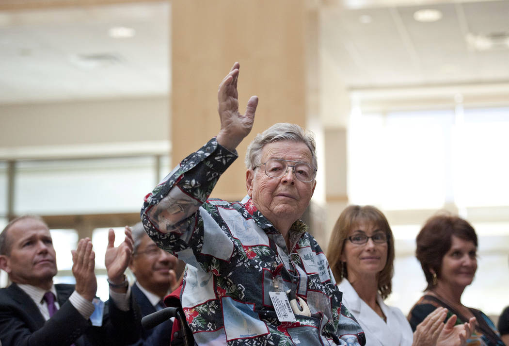 In this undated photo, Medtronic founder Earl Bakken waves as he's acknowledged by new CEO Omar Ishrak at the annual shareholders meeting at Medtronic's Fridley, Minn., headquarters. Medtronic sa ...