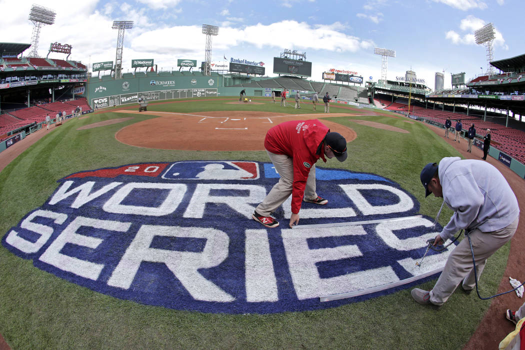 Grounds crew members paint the World Series logo behind home plate at Fenway Park, Sunday, Oct. 21, 2018, in Boston as they prepare for Game 1 of the baseball World Series between the Boston Red S ...