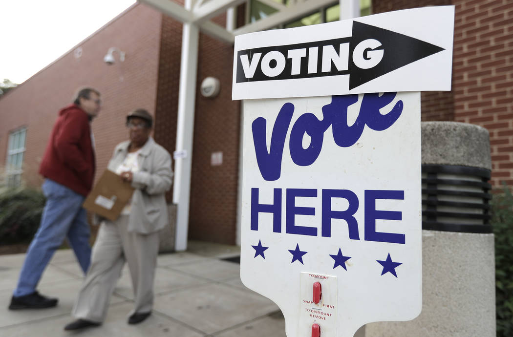 A voter arrives as a worker walks past during early voting at a polling place in Charlotte, N.C., Tuesday, Oct. 23, 2018. (AP Photo/Chuck Burton)