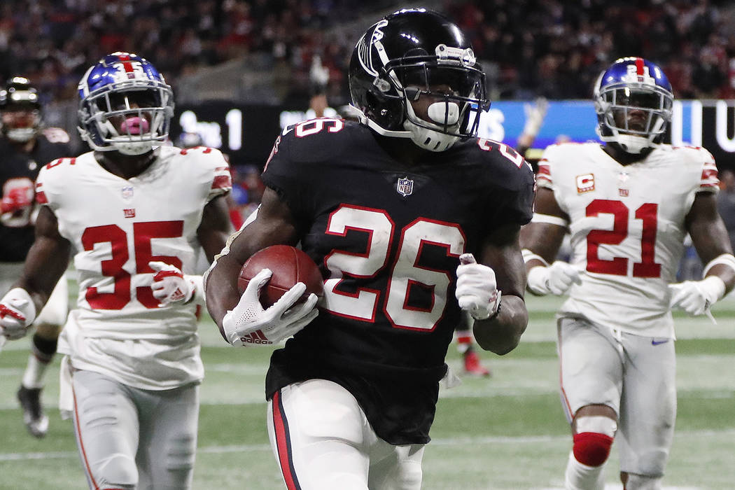 Atlanta Falcons running back Tevin Coleman (26) runs into the end zone for a touchdown against New York Giants free safety Curtis Riley (35) and strong safety Landon Collins (21) during the second ...