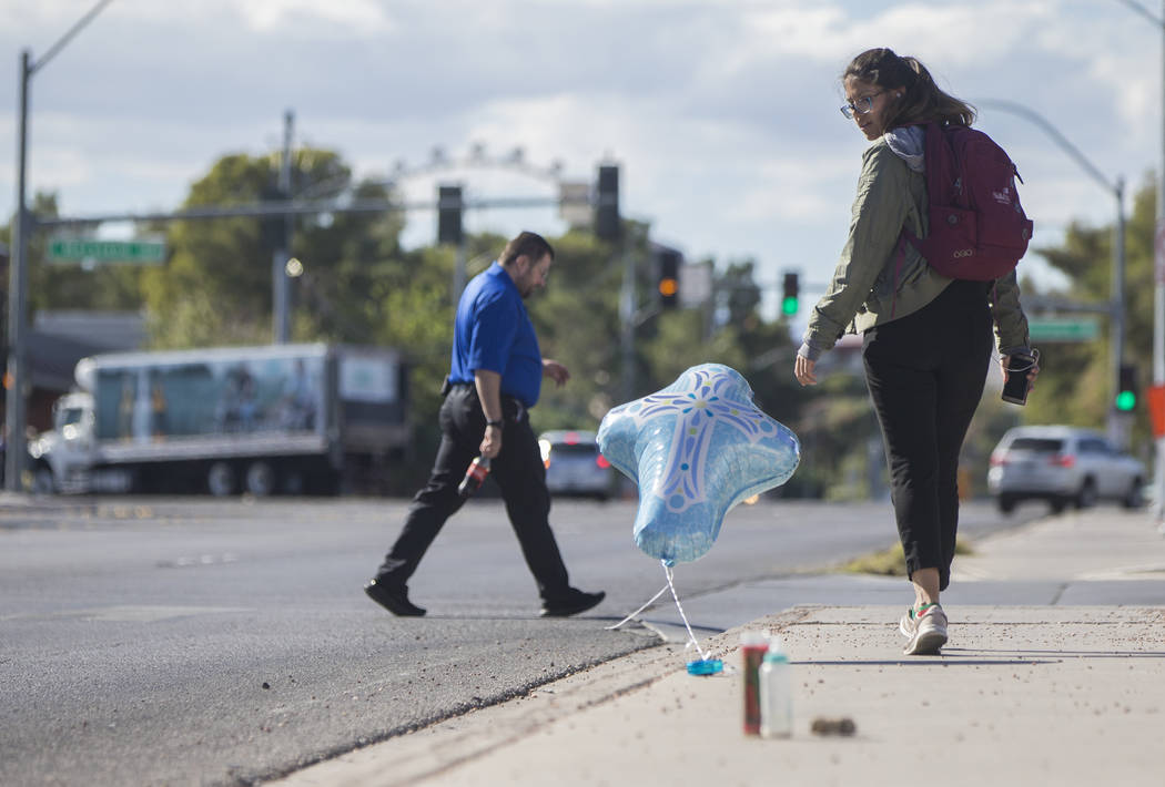 People walk by a makeshift memorial near East Katie Avenue and South Maryland Parkway for a family of four who was struck in the crosswalk Monday night, leaving a 4-year-old dead. Photo taken at t ...
