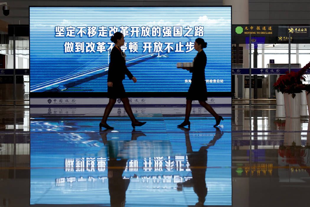 Hostesses walk by a billboard displaying the China-Zhuhai-Macau-Hong Kong Bridge ahead of the opening ceremony at the immigration building in Zhuhai in south China's Guangdong province, Tuesday, O ...