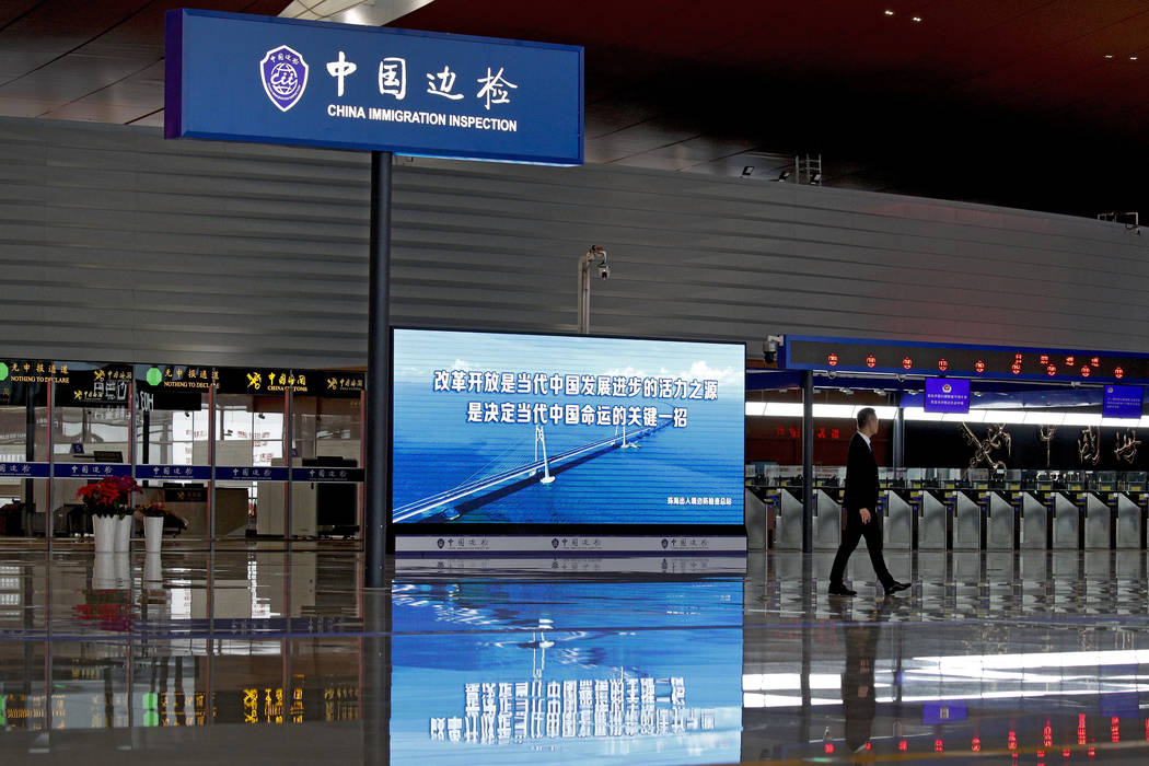 An officer walks by the immigration building for the China-Zhuhai-Macau-Hong Kong Bridge ahead of the opening ceremony in Zhuhai in south China's Guangdong province, Tuesday, Oct. 23, 2018. The br ...