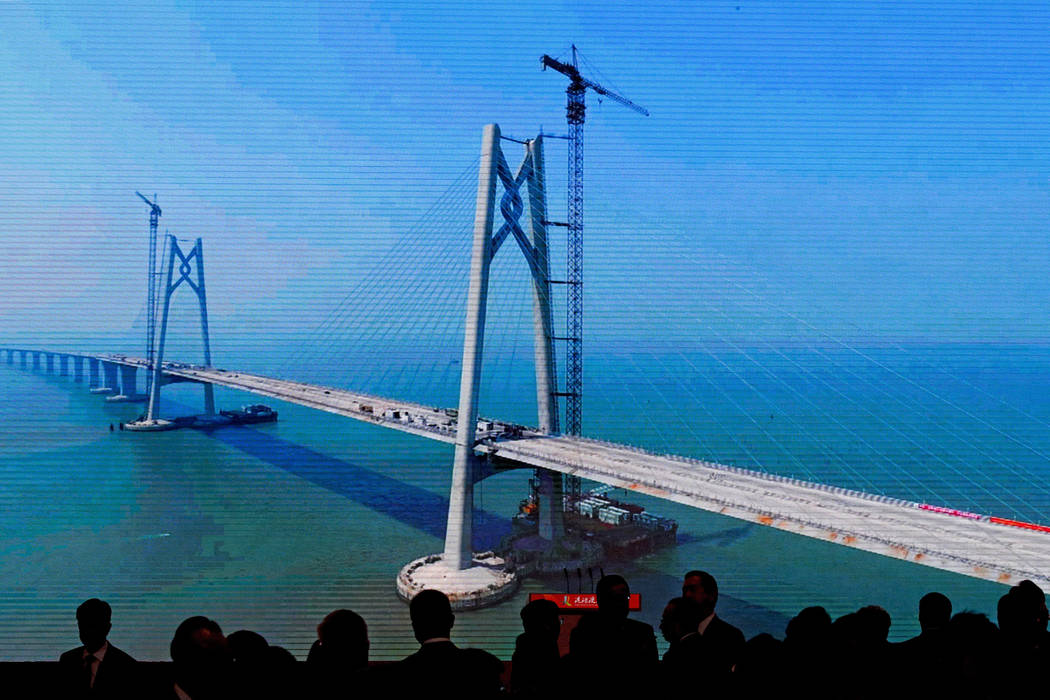 Invited officials are silhouetted on a projector screen showing the construction of the China-Zhuhai-Macau-Hong Kong Bridge ahead of the opening ceremony at the immigration building in Zhuhai in s ...