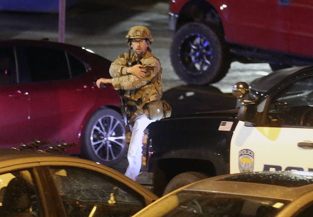 A law enforcement officer walks near the South Medical Tower on the University of Utah campus during a search for a man they say shot and killed a University of Utah student outside of a dormitory ...
