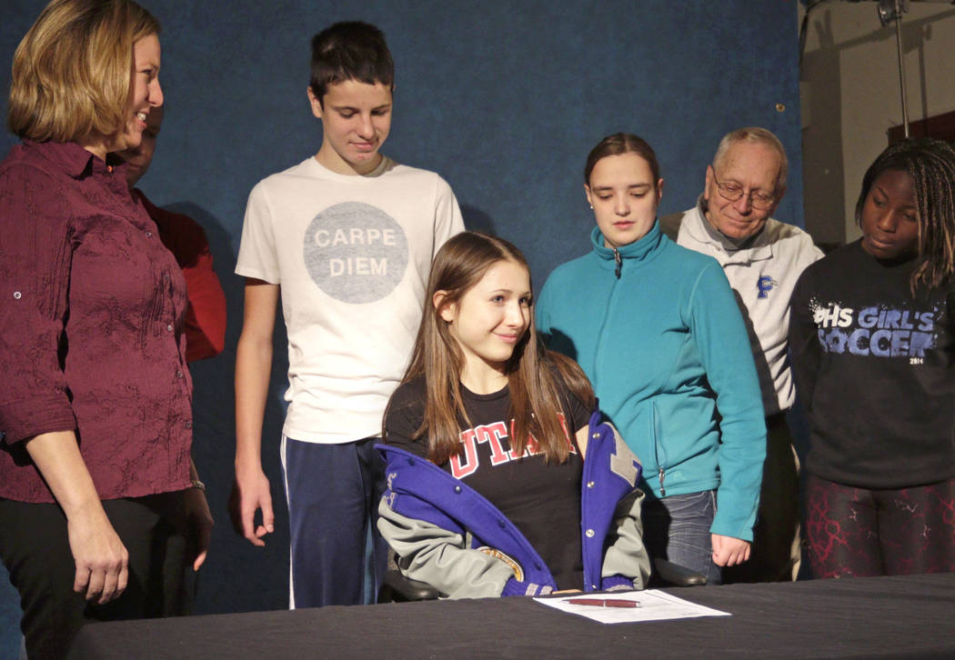 In the Nov. 19, 2014 photo, Pullman High School senior Lauren McCluskey is surrounded by her family before signing a letter of intent in Pullman, Wash., to compete in track for the University of U ...