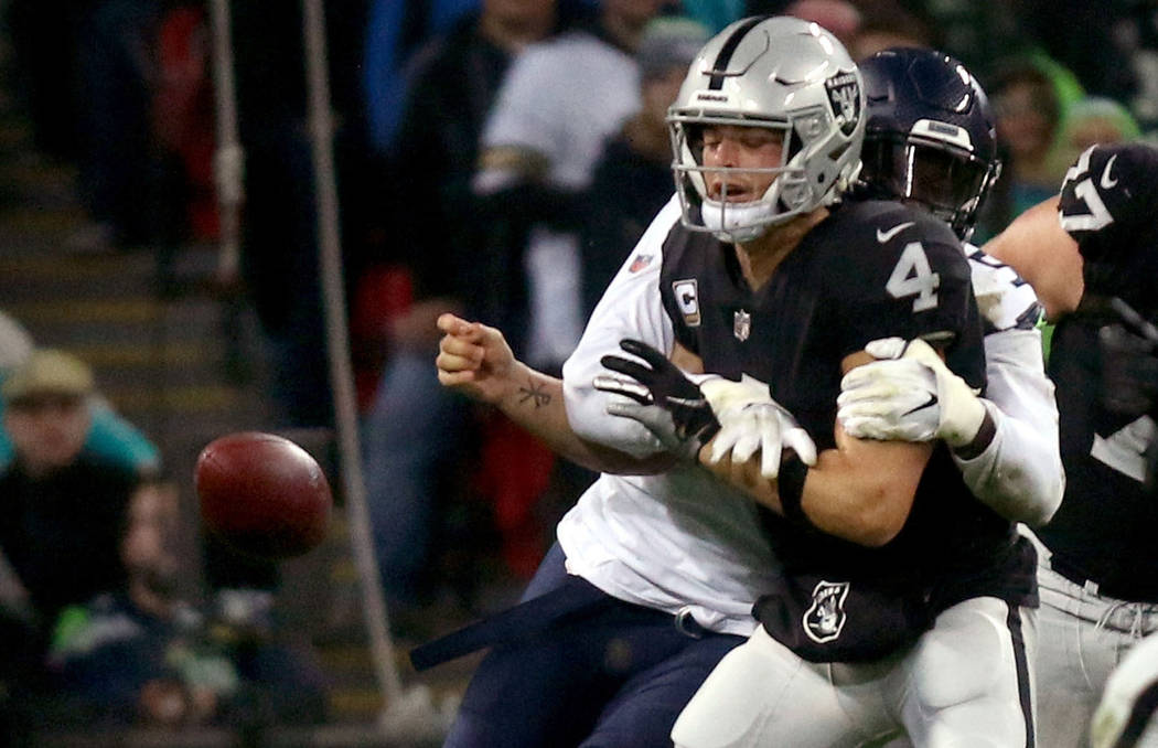 Oakland Raiders quarterback Derek Carr (4) is sacked by Seattle Seahawks defensive end Frank Clark (55) and fumbles the football during the first half of an NFL game at Wembley Stadium in London, ...