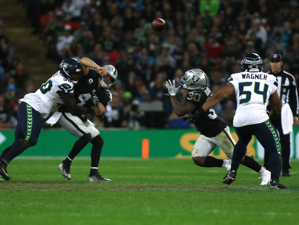 Oakland Raiders quarterback Derek Carr (4) is hit by Seattle Seahawks defensive tackle Jarran Reed (90) as he throws the football towards running back Jalen Richard (30) during the first half of a ...